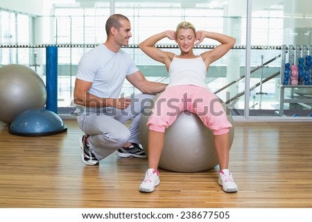 Full length of a male trainer assisting woman with abdominal crunches at the gym - stock photo