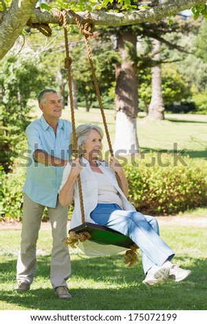 Full length of a mature couple at swing in the park