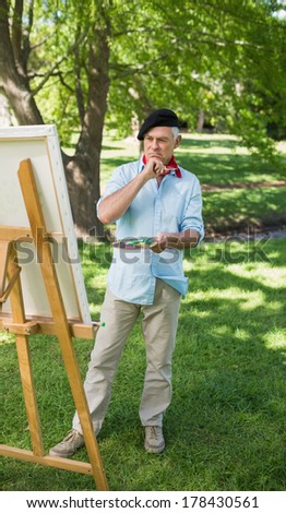 Full length of a mature man painting on canvas in the park - stock photo