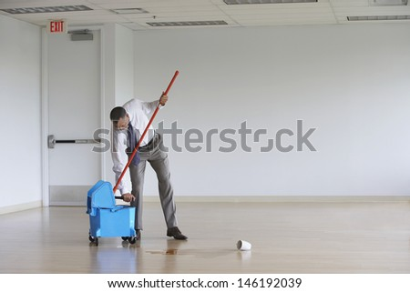 Full length of a middle aged businessman using mop in empty room - stock photo
