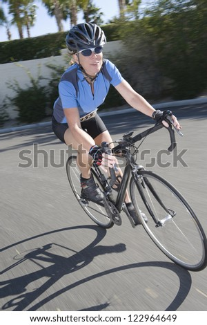Full length of a middle aged woman in sportswear riding bicycle on street - stock photo