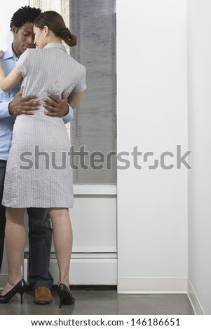 Full length of a multiethnic business couple embracing indoors - stock photo