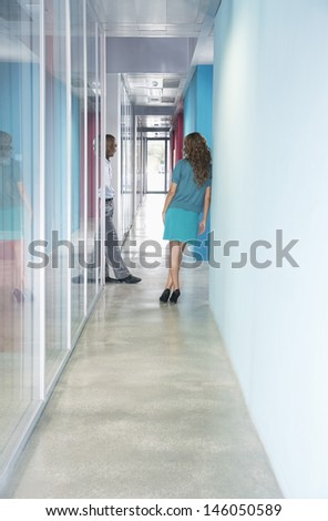 Full length of a multiethnic business couple talking the at end of corridor in office - stock photo