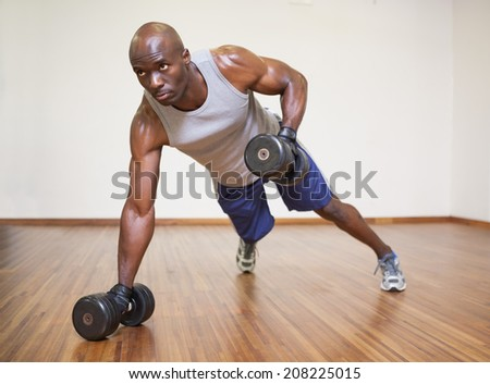 Full length of a muscular man doing push ups with dumbbells in gym - stock photo