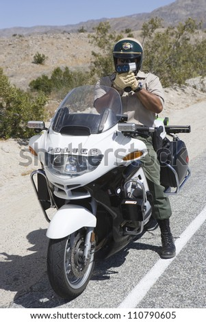 Full length of a police officer on motorbike monitoring speed though radar gun - stock photo