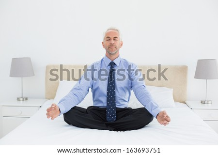Full length of a relaxed mature businessman sitting in lotus posture on bed at home - stock photo