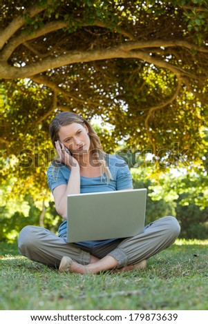 Full length of a relaxed young woman using laptop and mobile phone at the park