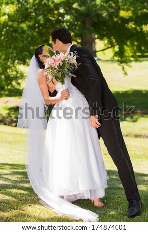 Full length of a romantic newlywed couple kissing in the park