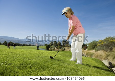 Full length of a senior woman playing golf with people in the background - stock photo