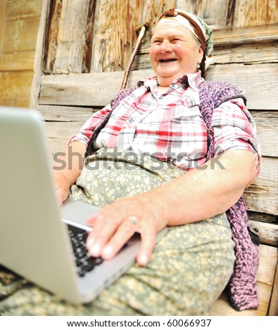 Full length of a senior woman sitting and using a laptop against - stock photo