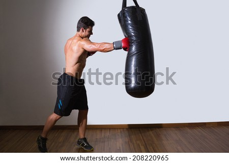 Full length of a shirtless muscular boxer with punching bag in gym - stock photo