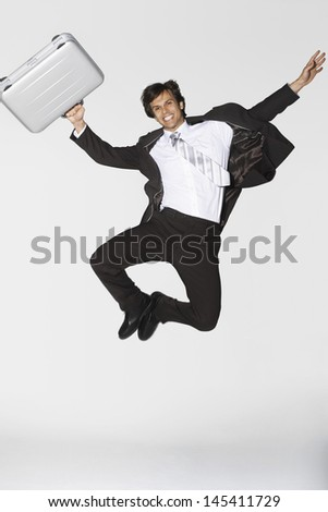 Full length of a smiling young businessman with briefcase jumping against white background - stock photo