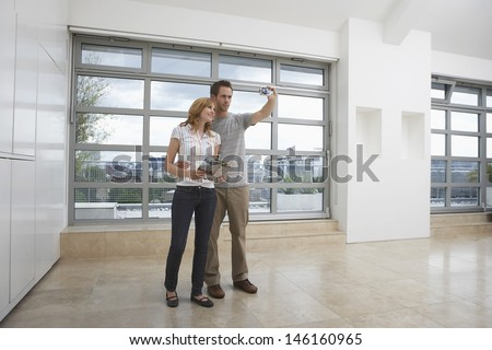 Full length of a smiling young couple photographing empty apartment - stock photo