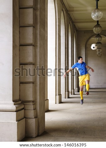 Full length of a soccer player kicking ball in portico - stock photo