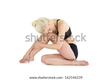 Full length of a sporty toned woman sitting down over white background - stock photo
