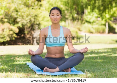 Full length of a sporty young woman in lotus pose with eyes closed at the park