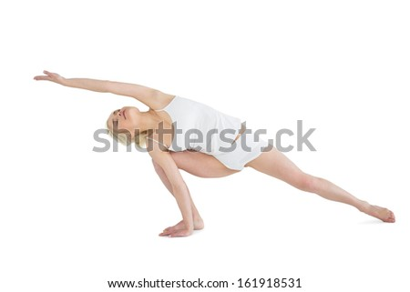 Full length of a sporty young woman practicing yoga over white background - stock photo