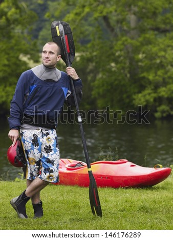 Full length of a thoughtful young man with kayak paddle standing on grass - stock photo