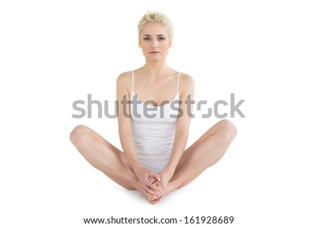 Full length of a toned young woman doing the butterfly stretch against white background - stock photo