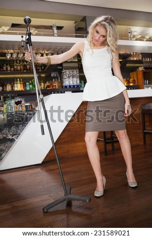 Full length of a woman singing into a microphone at the nightclub - stock photo