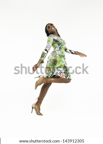 Full length of a young African American woman walking in heels against white background - stock photo