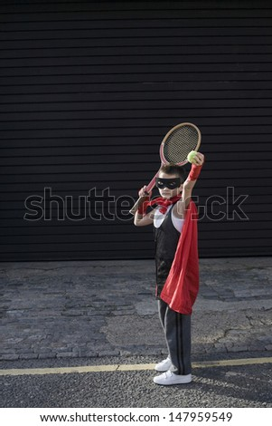 Full length of a young boy in costume with tennis racket - stock photo