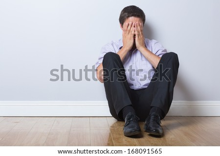 Full length of a young businessman sitting on floor with hands covering face in an empty room