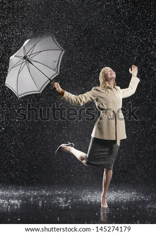 Full length of a young businesswoman in overcoat with umbrella enjoying the rain - stock photo