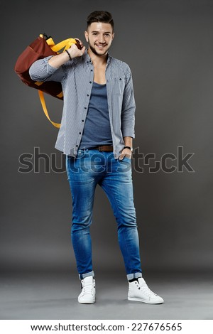Full length of a young caucasian student with bag - stock photo