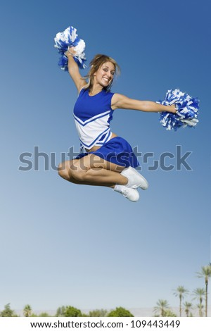 Full length of a young cheerleader jumping with pom-poms against sky - stock photo