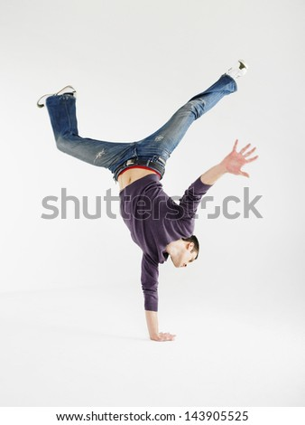 Full length of a young man doing one handed handstand against gray background - stock photo