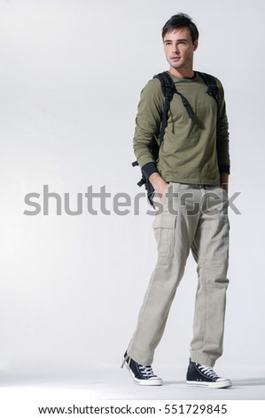 Full length of a young man in backpack walking in studio