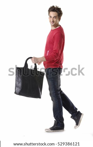 Full length of a young man in jeans and shirt ,bag walking in studio