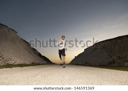Full length of a young man jogging on country street at dusk - stock photo