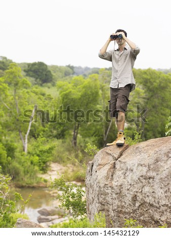 Full length of a young man on rock with binoculars looking at view - stock photo