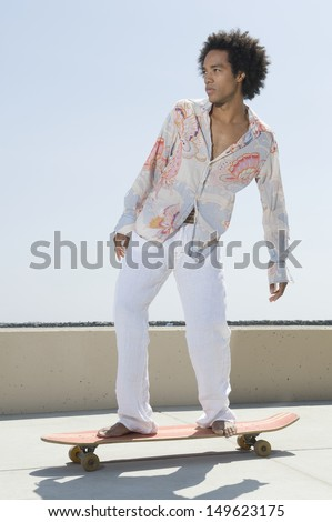 Full length of a young man on skateboard - stock photo