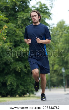 Full length of a young man running outdoors  - stock photo