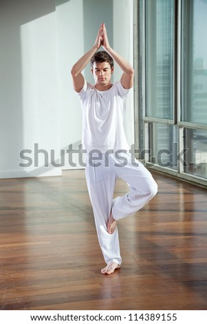 Full length of a young man standing in Tree Pose at gym
