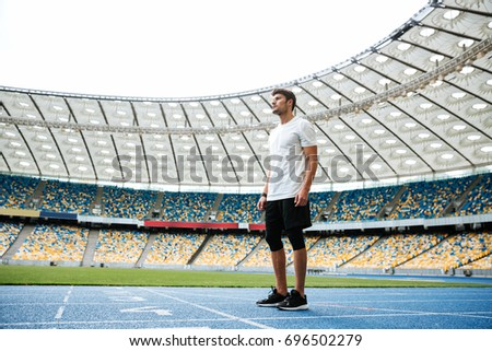 Full length of a young sportsman standing on a racetrack at the stadium