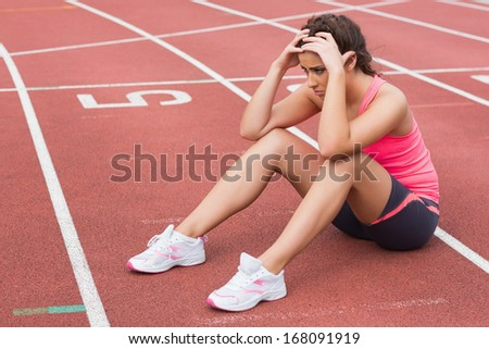 Full length of a young sporty woman sitting on the running track - stock photo