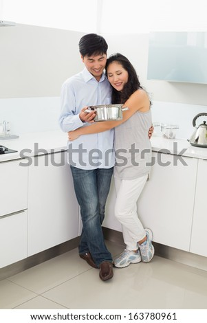 Full length of a young woman embracing man in the kitchen at home - stock photo