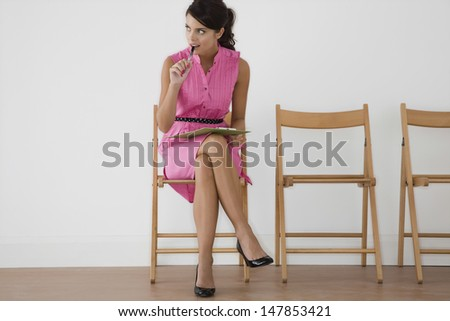 Full length of a young woman in pink dress with pen looking away at waiting room