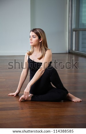 Full length of a young woman practicing yoga called Half Spinal Twist on wooden floor - stock photo