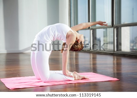 Full length of a young woman practicing yoga in Camel position on mat - stock photo