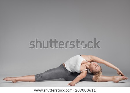 Full length of a young woman stretching body. Gray Background. - stock photo