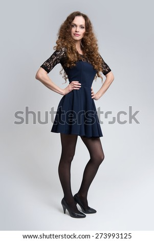 Full length of a young woman with long curly hair smiling - stock photo