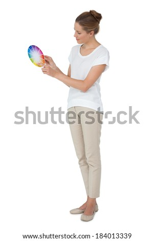 Full length of a young woman with paint samples over white background - stock photo