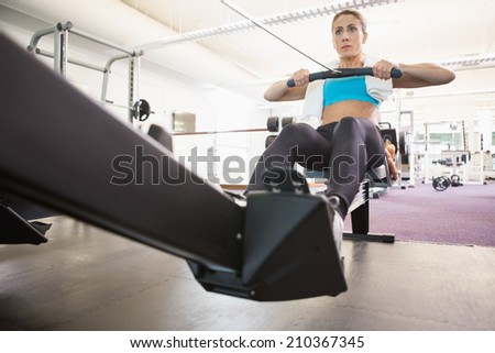 Full length of a young woman working on fitness machine at the gym - stock photo