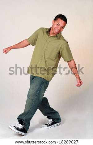 full length of African-American teen boy with great teeth - stock photo