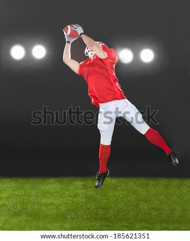 Full length of American football player jumping on field at night - stock photo